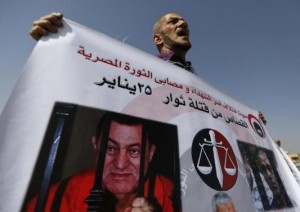 A man whose relatives were killed during the 2011 Egyptian revolution, holds a banner with pictures of former Egyptian President Mubarak as he shouts slogans outside the police academy on the outskirts of Cairo