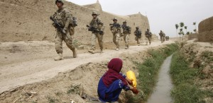 An Afghan girl watches as U.S. Army soldiers from 4-73 Cavalry Regiment, 82nd Airborne Division walk by during a mission in Zhary district of Kandahar province