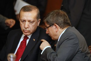 Turkey's FM Davutoglu speaks with Turkish PM Erdogan during a meeting at the government palace in Tunis