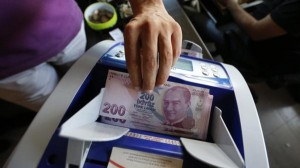 A money changer uses a machine to count Turkish liras in the border city of Hatay