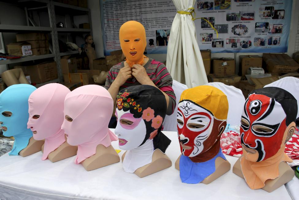 Zhang Shifan tries on a face-kini mask as she demonstrates products at exhibition in Qingdao