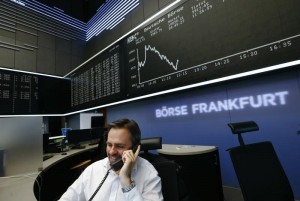 A trader is pictured at his desk in front of the German share price index DAX board at the Frankfurt stock exchange