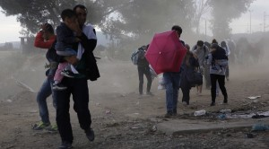 Syrian refugees try to protect themselves from gusts of wind and dust as they cross Greece's border with Macedonia
