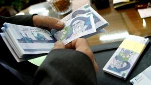 An Iranian bank teller counts new 20,000 rial notes at Iran's Central Bank
