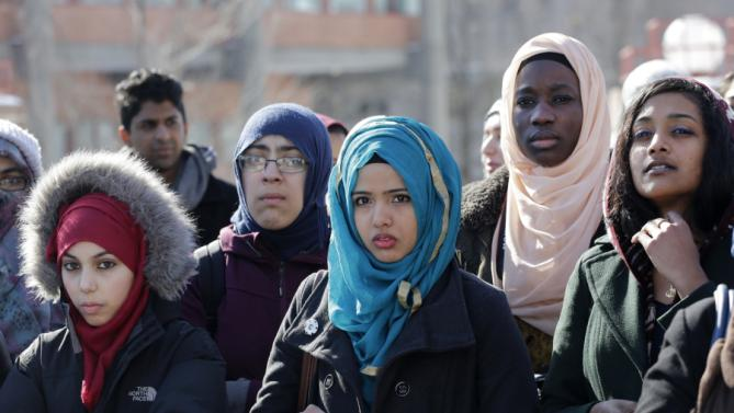 Students at Queens College in New York gather for a vigil, Wednesday, Feb. 18, 2015, in honor of three Muslim students killed recently near the University of North Carolina. President Barack Obama gathered police leaders, lawmakers and mayors from around the world Wednesday to address the threat of violent extremism at a White House summit that was far from what Obama originally envisioned. Planned for last October, the summit never happened before the midterm elections. In the months since, the situation has just gotten worse, with the Islamic State group metastasizing and European cities learning firsthand that extremism's reach is not confined to the Middle East. (AP Photo/Mark Lennihan)