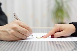 husband signing divorce agreement and woman push away weeding ring