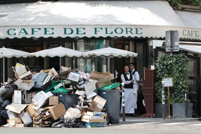A waiter stands near a pile of rubbish bags in front of the Cafe de Flore in Paris during a strike of garbage collectors and sewer workers of the city of Paris to protest the labour reforms law proposal, France, June 8, 2016.  REUTERS/Charles Platiau